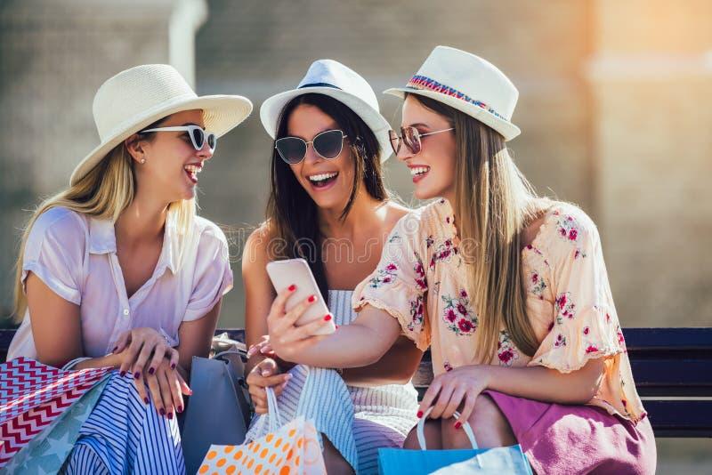 Trois filles avec les sacs à provisions colorés utilisant les téléphones intelligents photographie stock