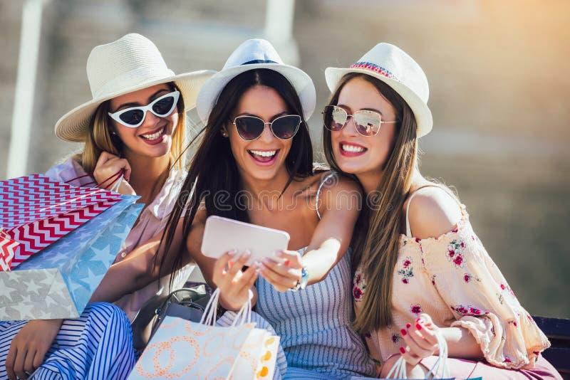 Trois filles avec les sacs à provisions colorés utilisant les téléphones intelligents photographie stock libre de droits