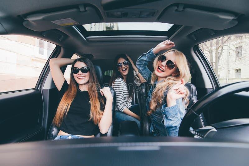 Trois filles conduisant dans une voiture convertible et ayant l'amusement, écoutent musique et dansent images libres de droits