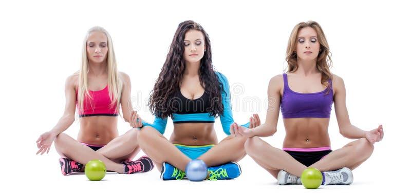 Trois filles décontractées méditant en position de lotus photos stock