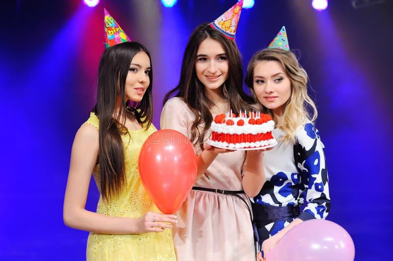 Trois filles dans des chapeaux et des ballons et gâteau de fête à disposition photo libre de droits