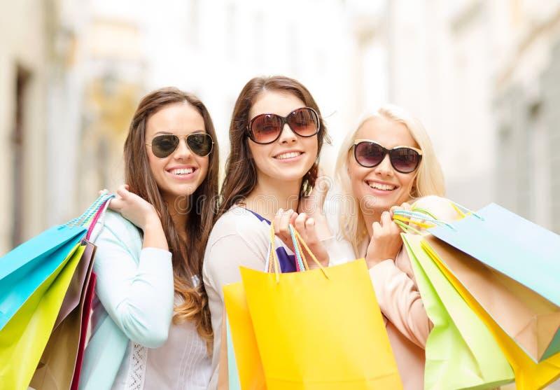 Trois filles de sourire avec des paniers dans la ville photographie stock libre de droits
