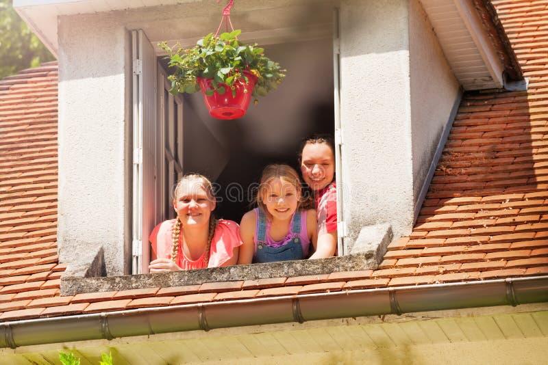 Trois filles de sourire dans la fenêtre ouverte de grenier photo stock