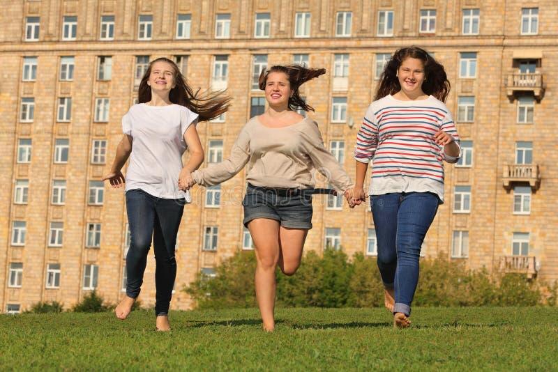 Trois filles de sourire exécutées à l'herbe photo libre de droits