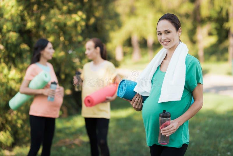 Trois filles enceintes sont venues au parc sur la forme physique Une fille dans un T-shirt vert posant avec une bouteille de spor photos libres de droits