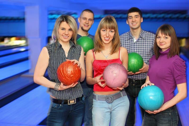 Trois filles et deux hommes retiennent la bille pour le bowling images stock