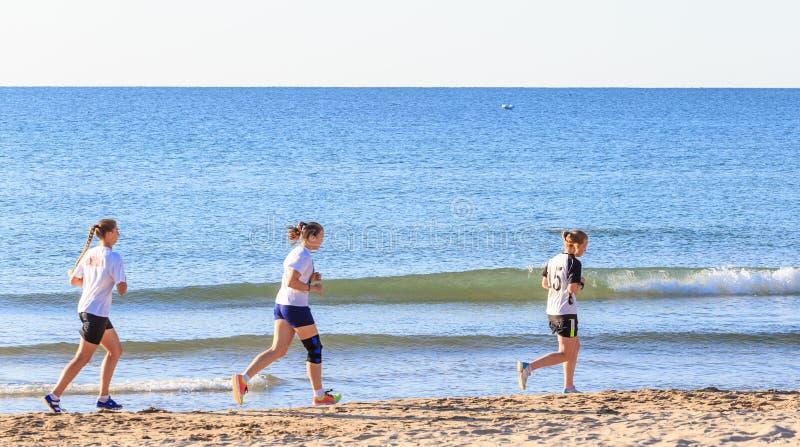 Trois filles exécutent sur la plage photo stock