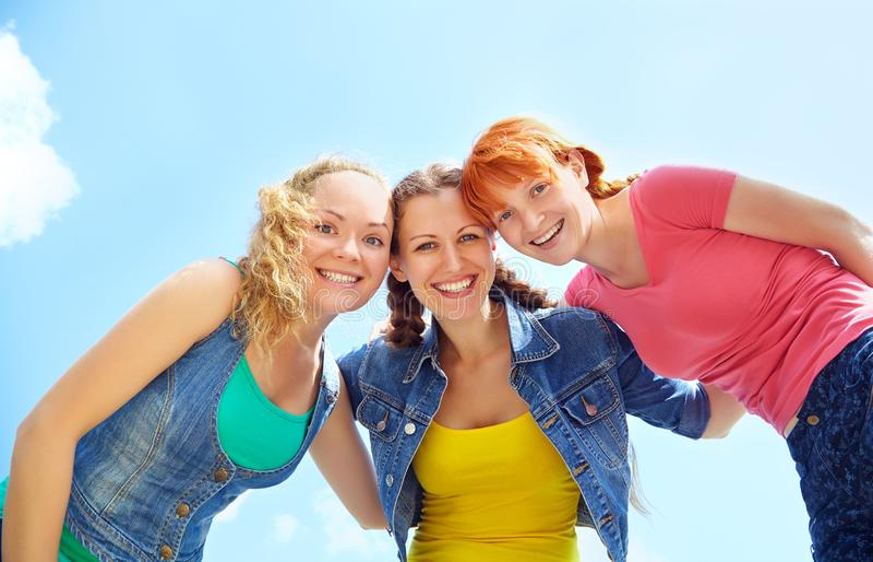 Trois filles heureuses regardant l'appareil-photo et rire embrassement de filles Vew de dessous image stock