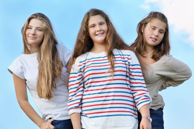 Trois filles heureuses restent ensemble image stock