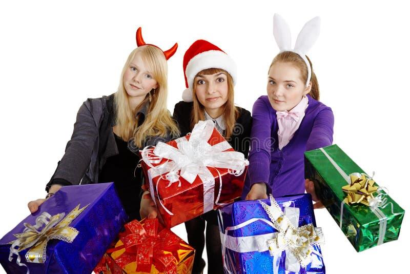 Trois filles remettent les cadeaux d'an neuf images libres de droits