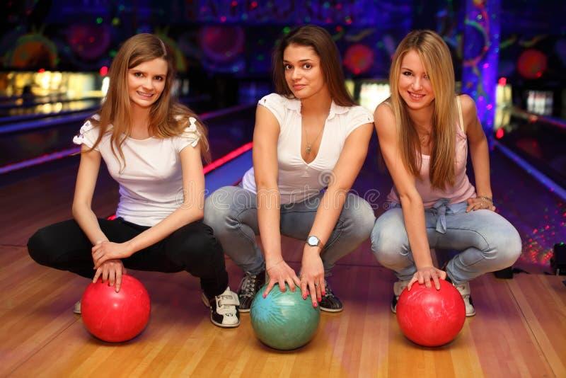 Trois filles s'asseyent avec des billes dans le club de bowling photo stock