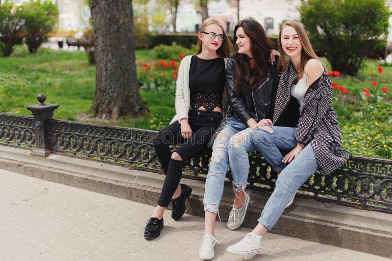 Trois filles s'asseyent sur le fond de parc images stock