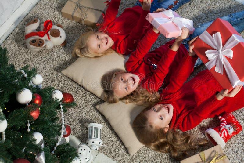 Trois filles se trouvent près d'un arbre de Noël avec l'hiver de vacances de nouvelle année de cadeaux image stock
