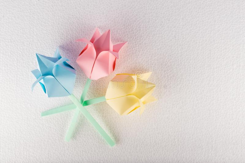 Trois fleurs d'origami sur le fond texturisé blanc photo stock