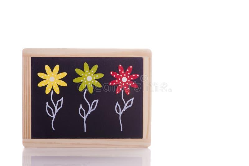 Trois fleurs sur le tableau noir - ressort photographie stock