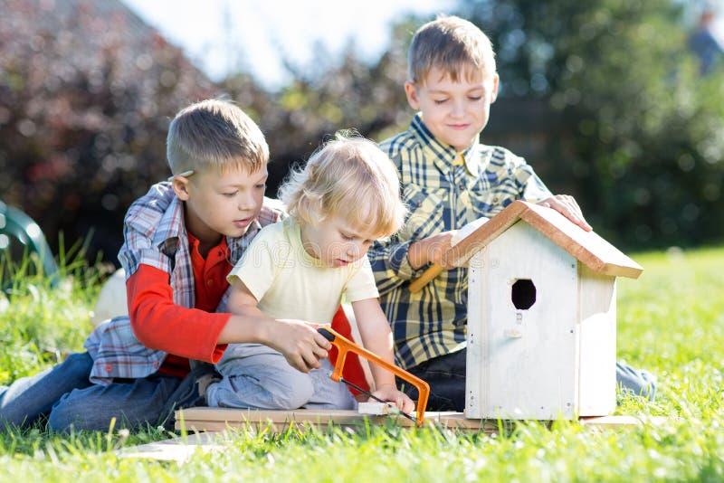 Trois frères de garçons d'enfants faisant la volière en bois à la main photographie stock