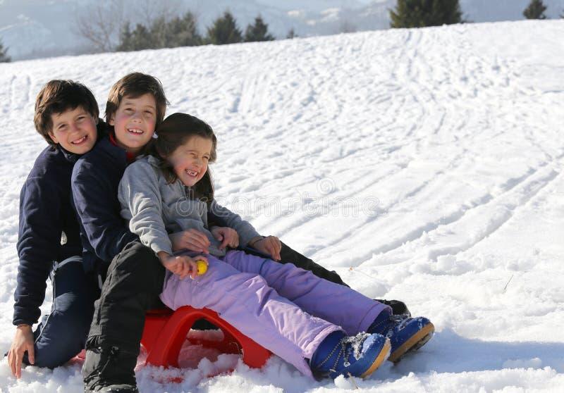Trois frères sur le traîneau dans la neige en hiver photographie stock libre de droits