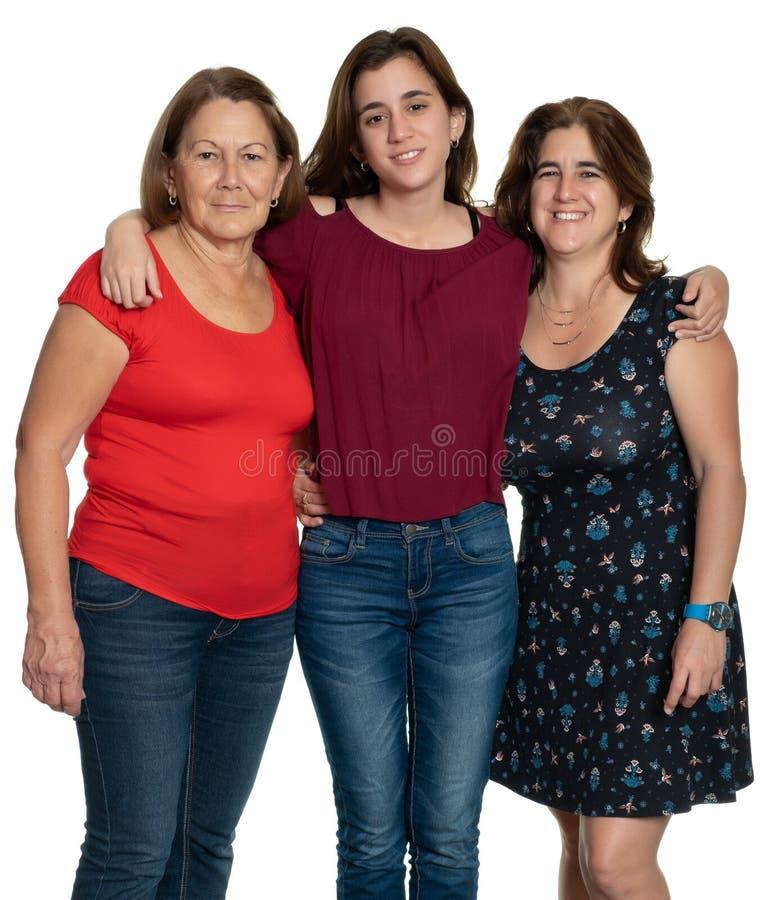 Trois générations des femmes latines souriant et étreignant - sur un fond blanc images stock