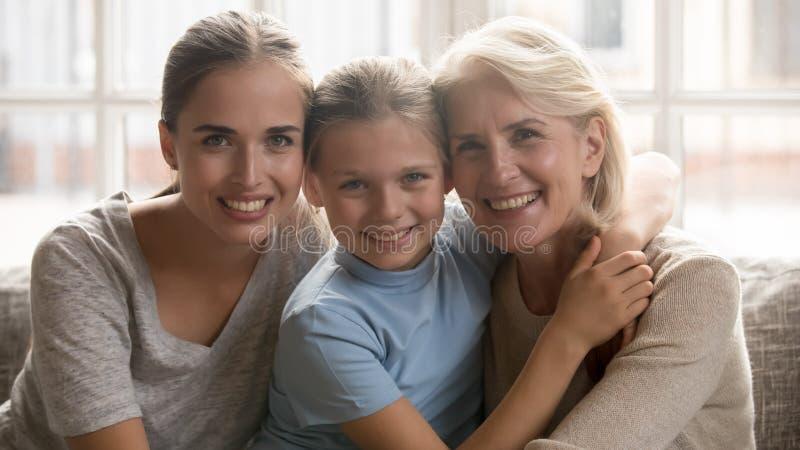Trois générations des femmes s'asseyant sur le divan regardant la caméra photographie stock