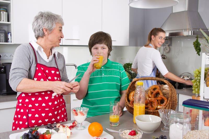 Trois générations vivant ensemble - famille heureuse faisant cuire le togethe image stock