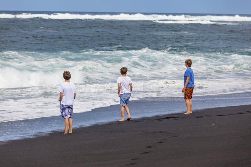 Trois garçons de l'adolescence marchent le long d'une plage volcanique noire photographie stock