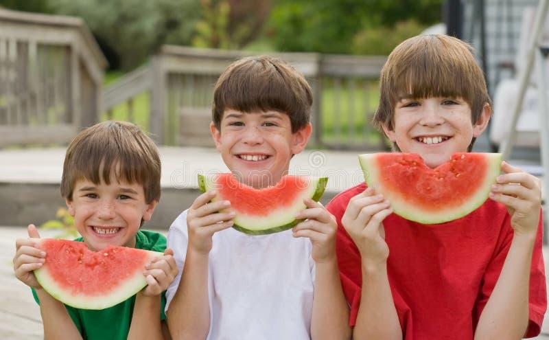 Trois garçons mangeant la pastèque photos libres de droits
