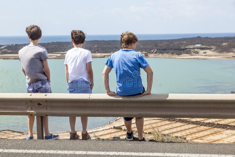 Trois garçons se penchant au rail de guide images stock
