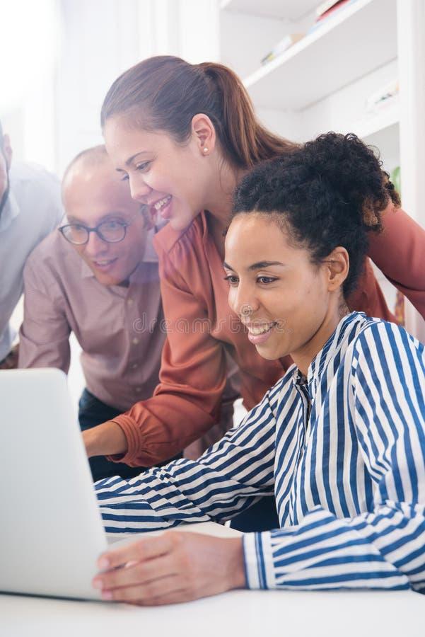 Trois gens d'affaires autour d'un ordinateur portable image stock