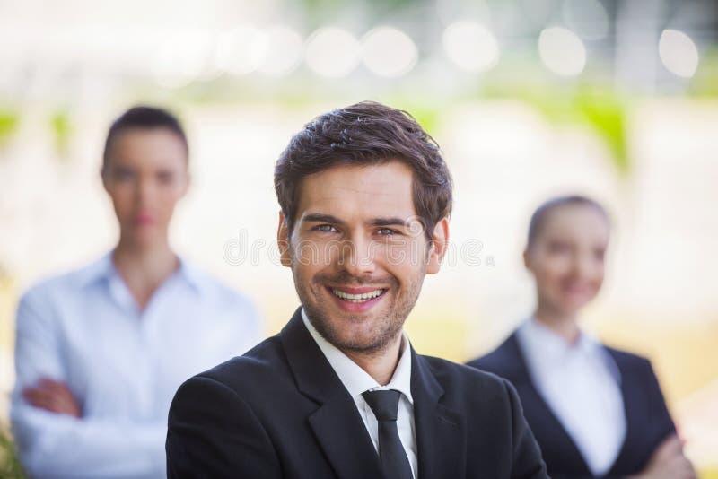 Trois gens d'affaires de sourire se tenant dehors photographie stock