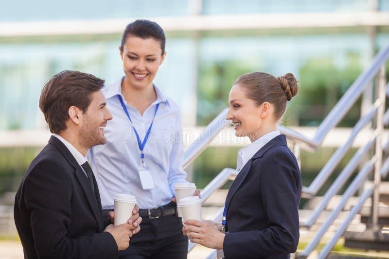 Trois gens d'affaires de sourire se tenant sur des escaliers images stock