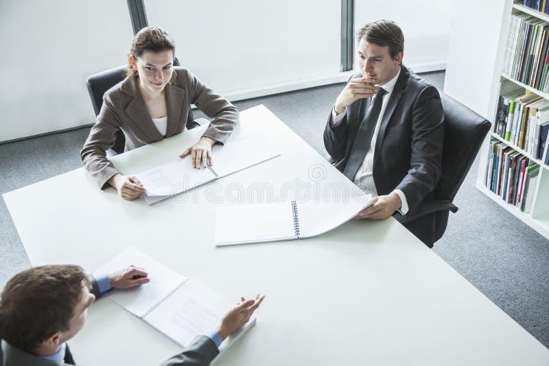 Trois gens d'affaires s'asseyant autour d'une table et ayant une réunion d'affaires, vue courbe photographie stock libre de droits