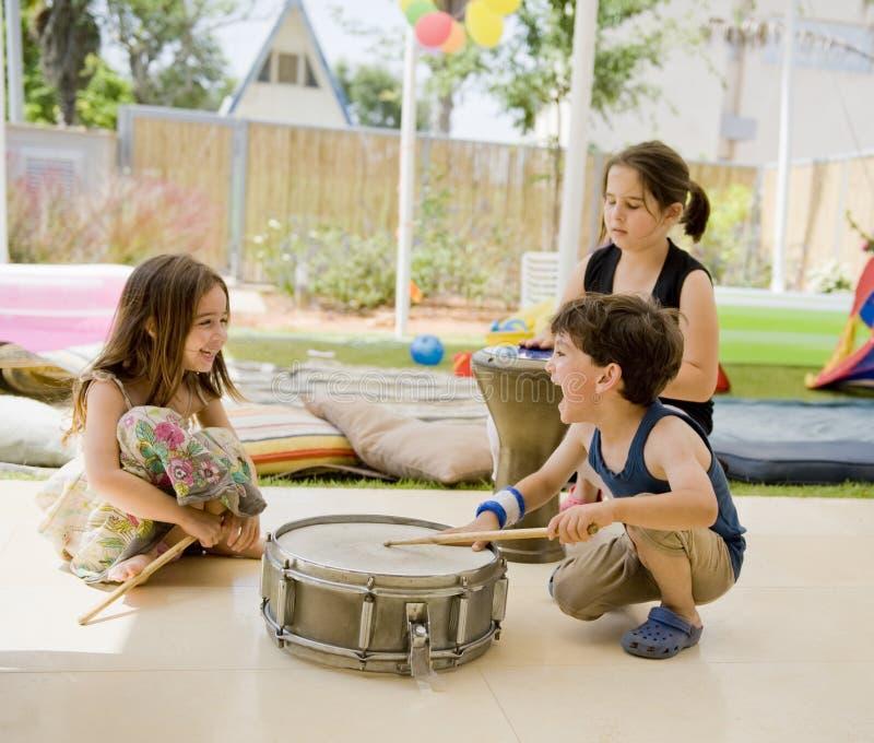 Trois gosses ayant l'amusement avec des tambours photographie stock libre de droits