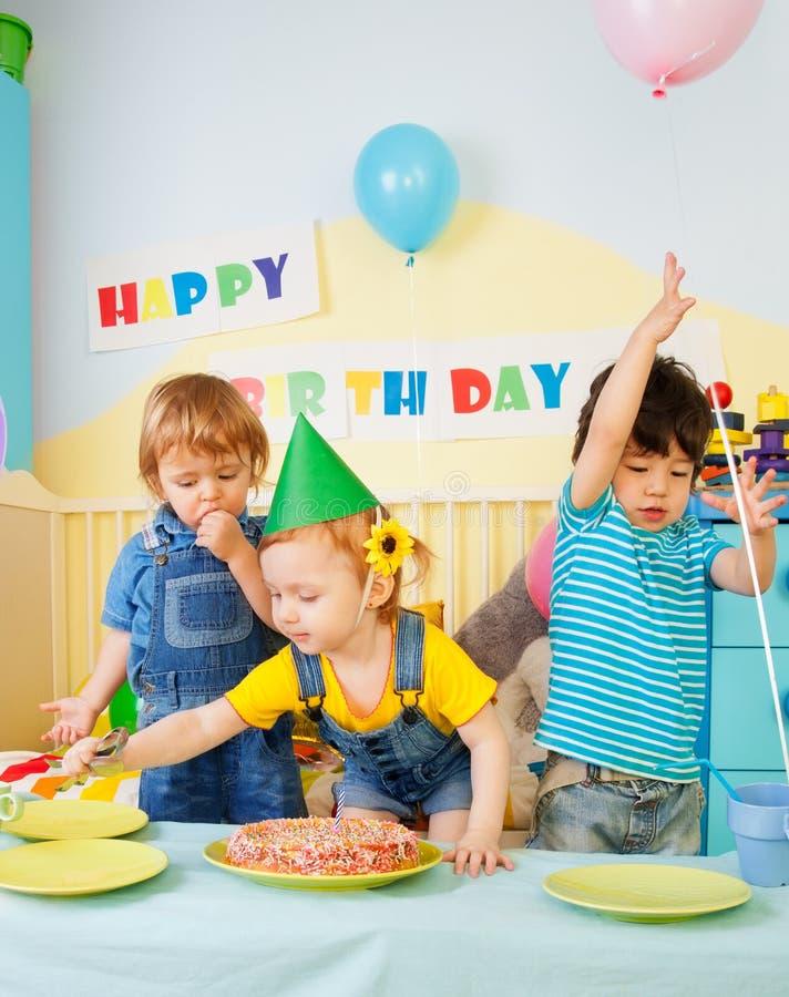 Trois gosses ayant l'amusement sur la fête d'anniversaire photos libres de droits