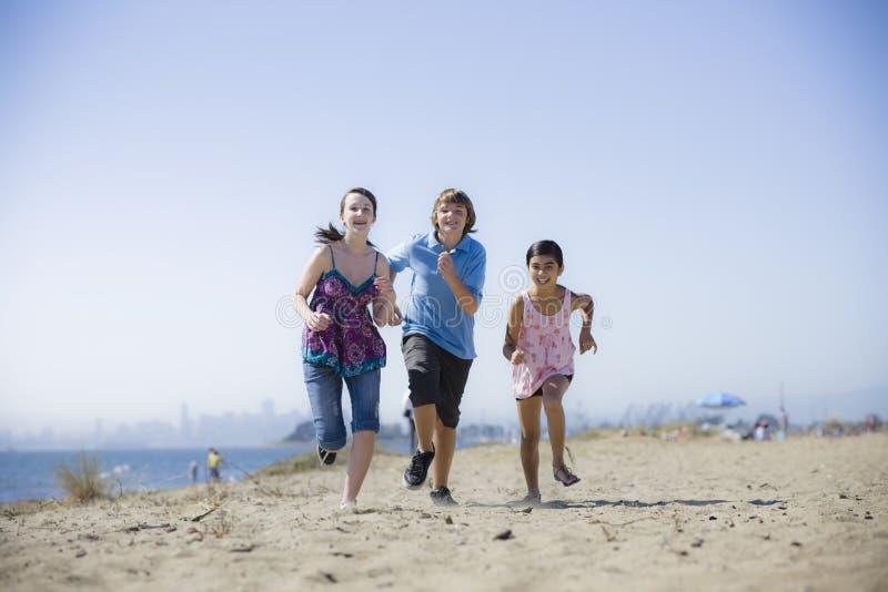 Trois gosses exécutant sur la plage image libre de droits