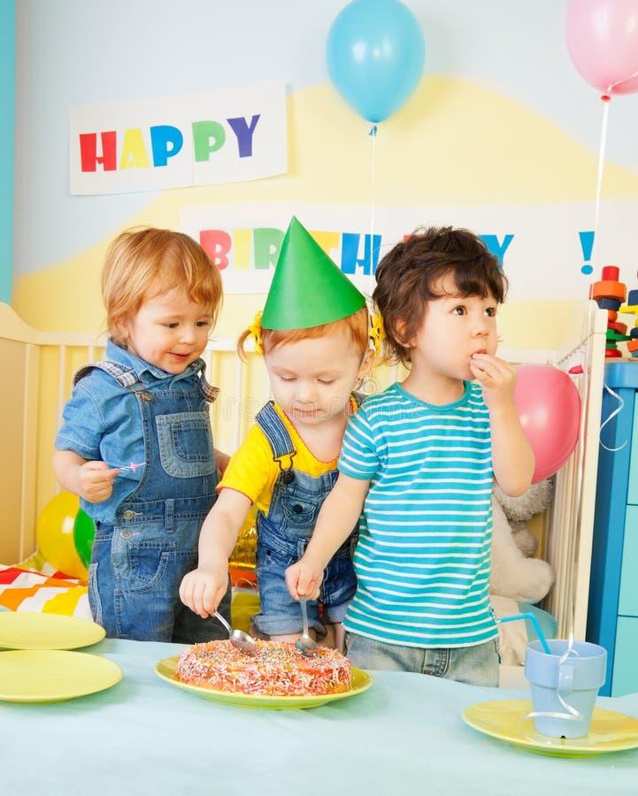 Trois gosses mangeant le gâteau sur la fête d'anniversaire image stock