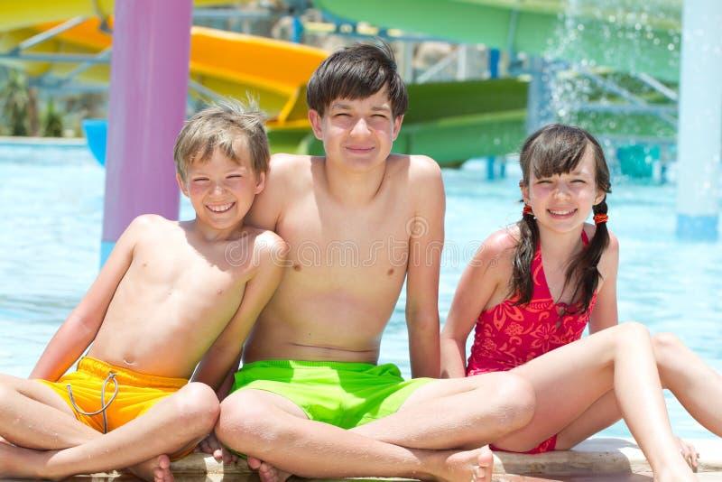 Trois gosses par le poolside photographie stock
