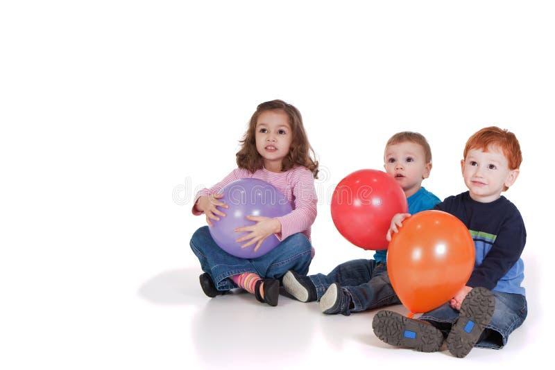 Trois gosses s'asseyant avec des ballons de réception photos libres de droits