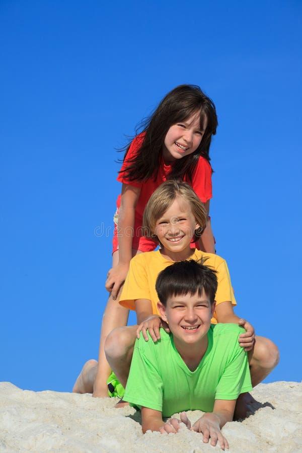 Trois gosses sur la plage photo stock