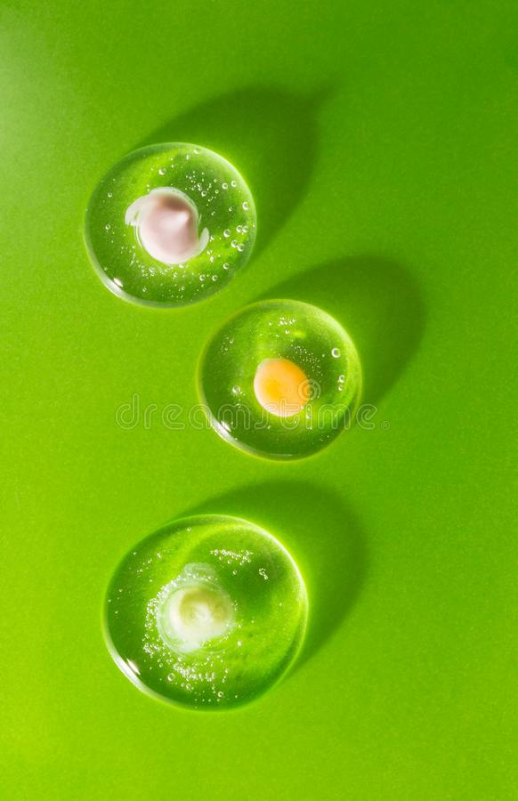 Trois gouttes de gel clair cosmétique avec divers écrème sur le fond vert Le concept de la compatibilité biologique de images stock