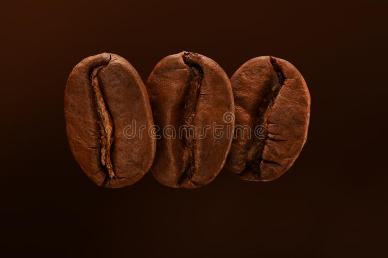Trois grains de café rôtis frais sur un fond brun Fermez-vous, macro Carte postale, bannière image libre de droits
