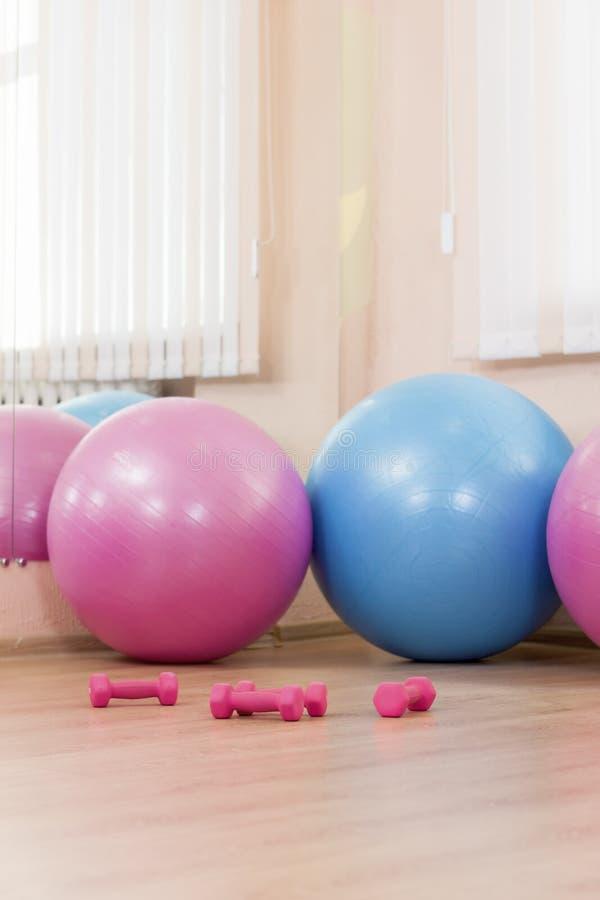 Trois grand Fitballs avec des Barbells sur le plancher au centre de fitness de sport à l'intérieur images libres de droits