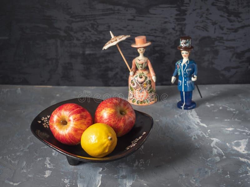 Trois grandes pommes rouges dans un vase noir et de petites figures des poupées de Gorodetz à l'arrière-plan à un arrière-plan re photo stock