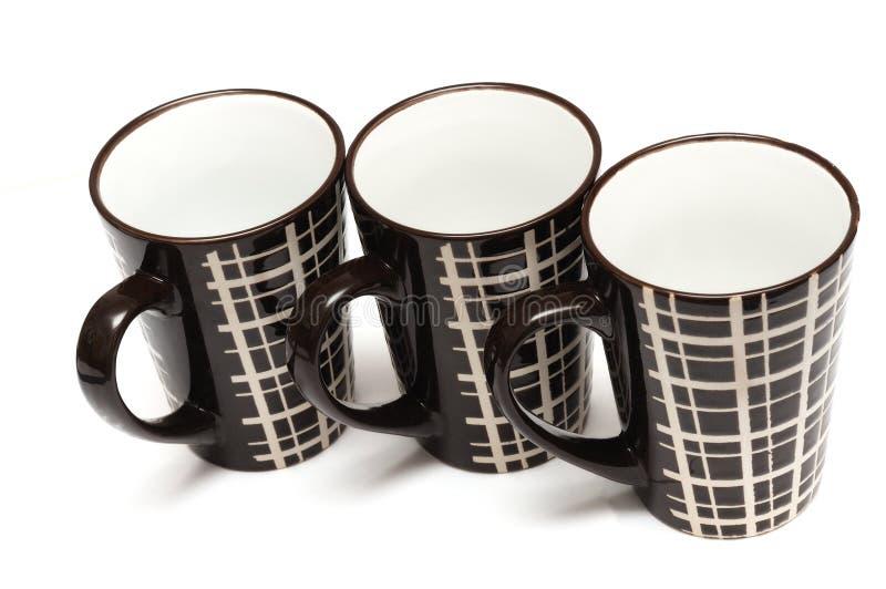 Trois grandes tasses de café brunes foncées grandes identiques avec les lignes simples conçoivent photo stock