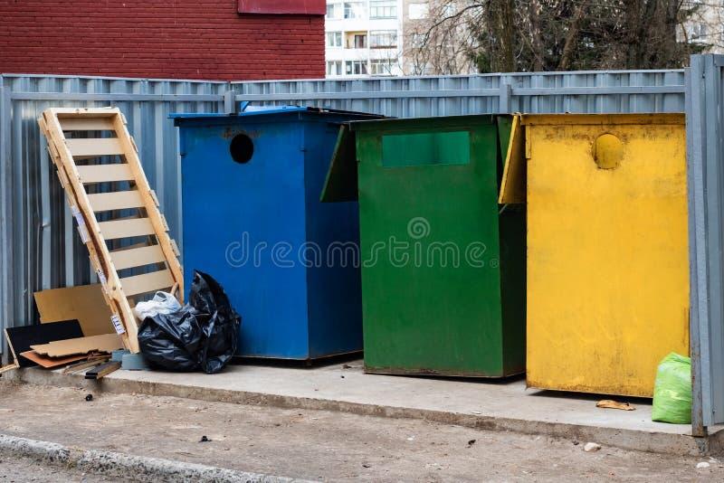 Trois grands poubelles et sacs de déchets colorés images stock