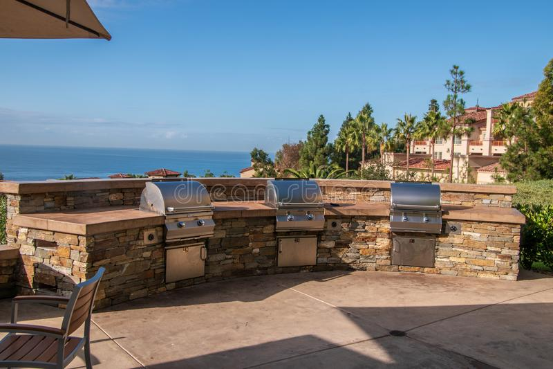 Trois grils de barbecue de gaz construits dans un mur en pierre sur un patio donnant sur l'océan et une station de vacances photos libres de droits