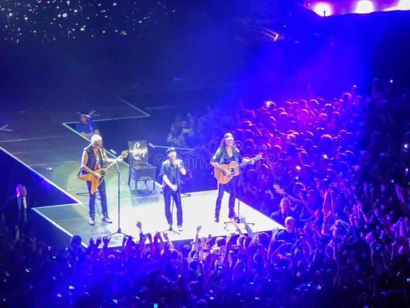 Trois guitaristes de groupe de rock de scorpions jouant sur la scène au milieu d'une foule photos stock