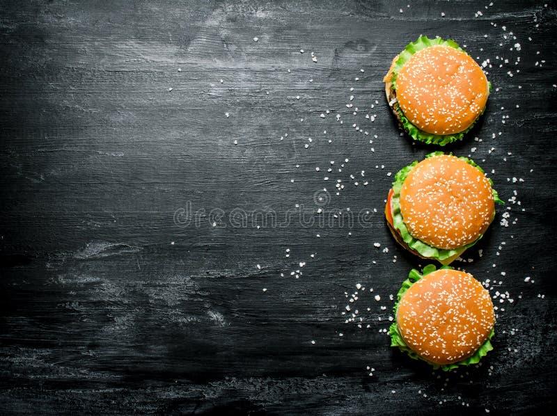 Trois hamburgers avec de la viande, le fromage et les légumes frais image stock