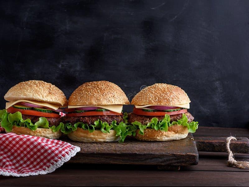 Trois hamburgers avec des légumes sur un conseil en bois brun photos stock