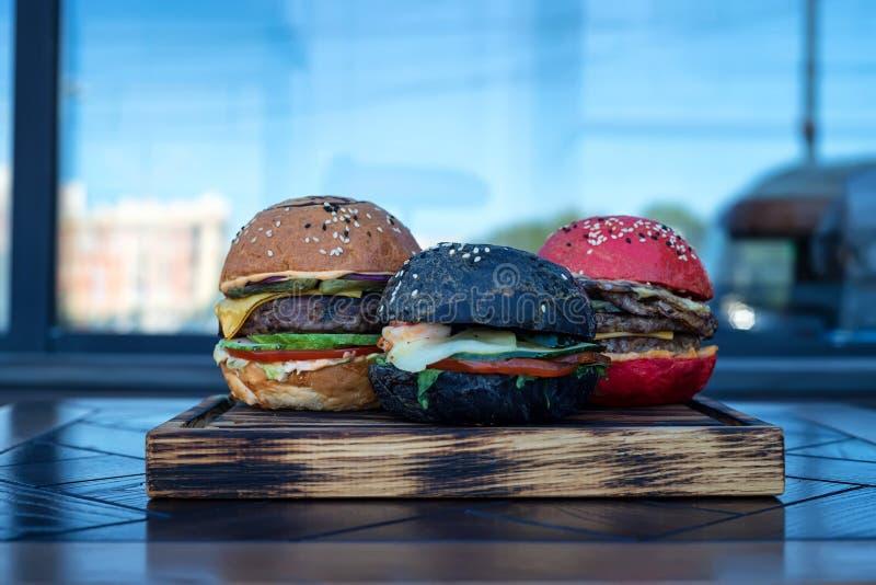 Trois hamburgers différents sur le conseil en bois images libres de droits