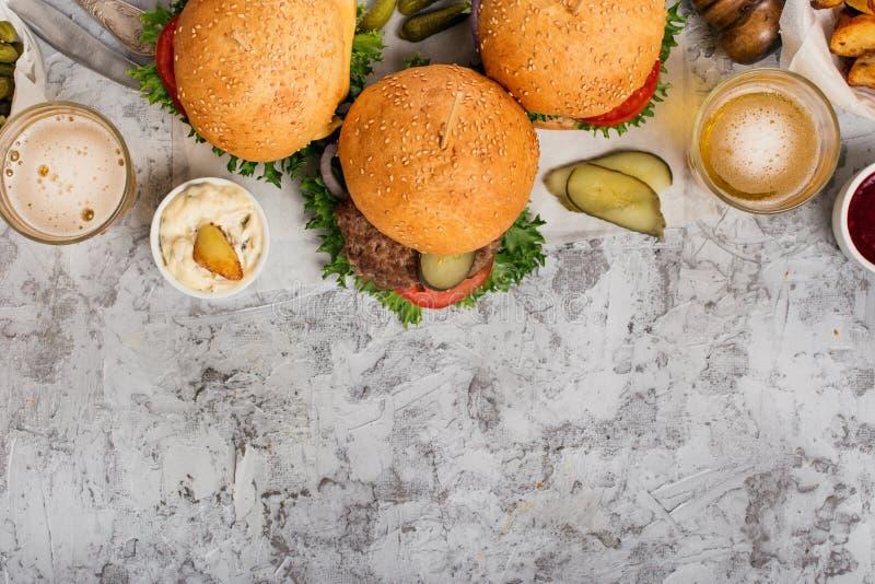 Trois hamburgers et bières blondes allemandes différents faits maison frais image stock